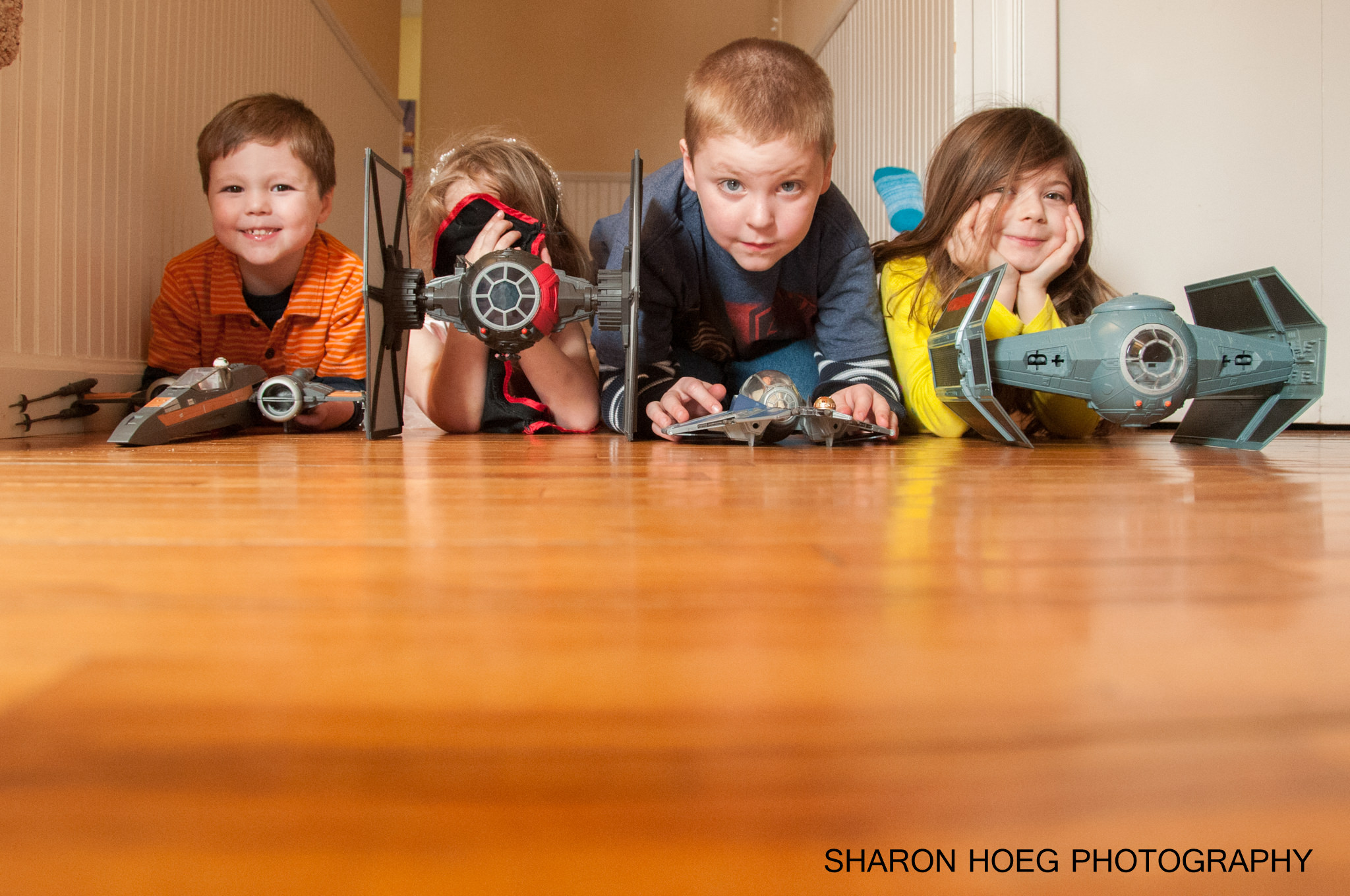 Siblings laying on the floor with space toys, Livonia Family Photographer