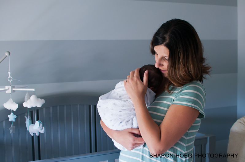 mom holding baby in nursery, northville family photographer