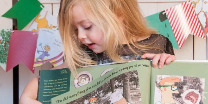 Blonde girl showing a book, South Lyon Child Photography