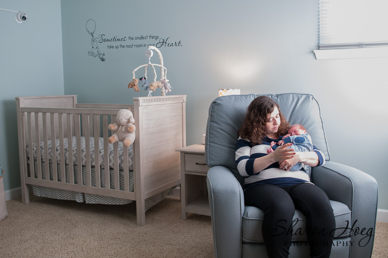 mom sitting in winnie the pooh nursery with new baby, South Lyon Newborn Photographer