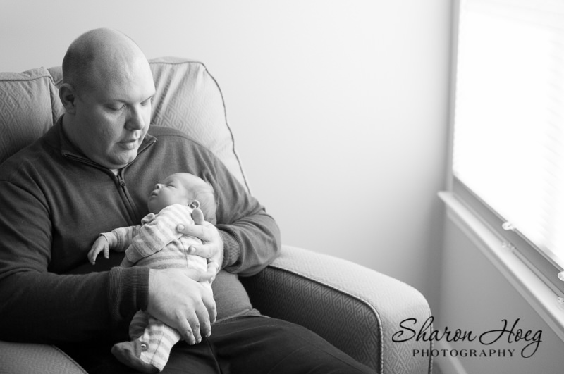 dad cuddling newborn baby in nursery, South Lyon Family Photography