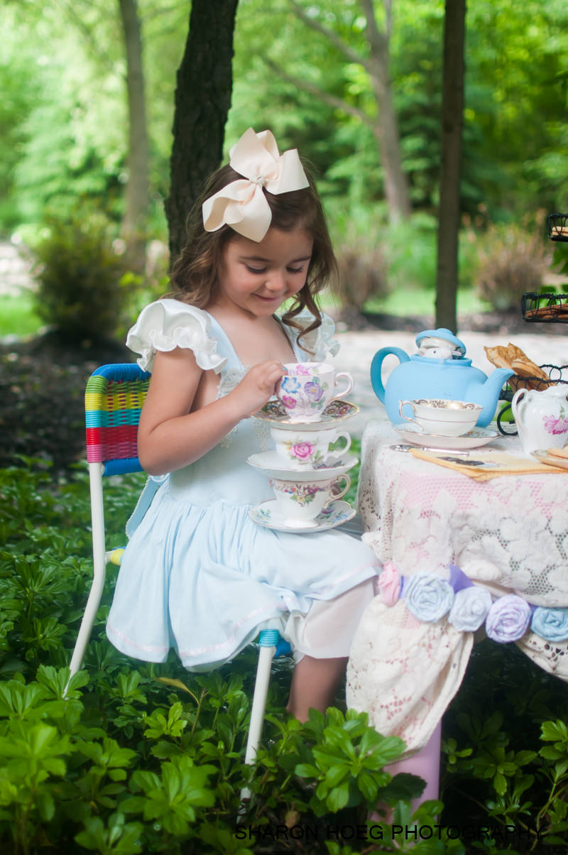 young girl holding a stack of tea cups, Michigan Disney Inspired Photography