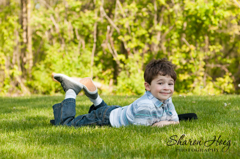 young boy laying in the grass with his feet up, Northville Child Photography