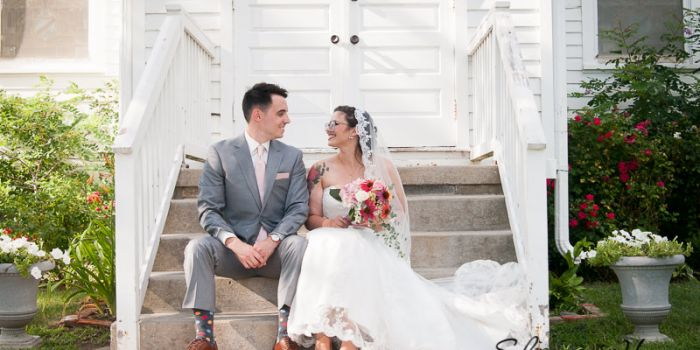 couple sitting on the steps of the chapel, Greenmead Wedding Photography