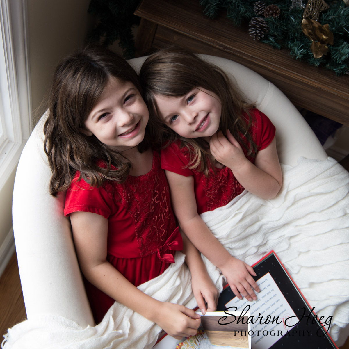 2 girls in red dresses in a chair with a santa book, Holiday Mini Sessions 2017