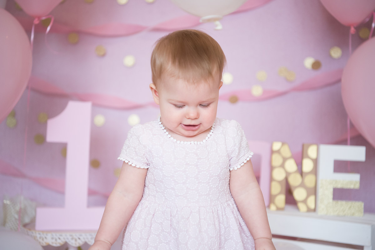 sweet one year old girl in pink dress looking down, Northville photography