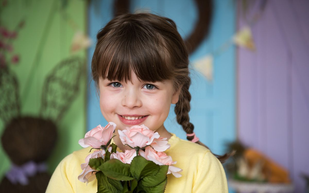 young girl with braids holding flowers, Northville Photography spring sessions