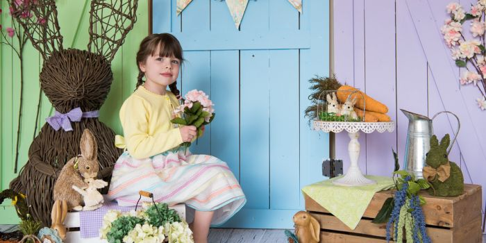 happy girl holding flowers sitting on a crate, spring mini sessions