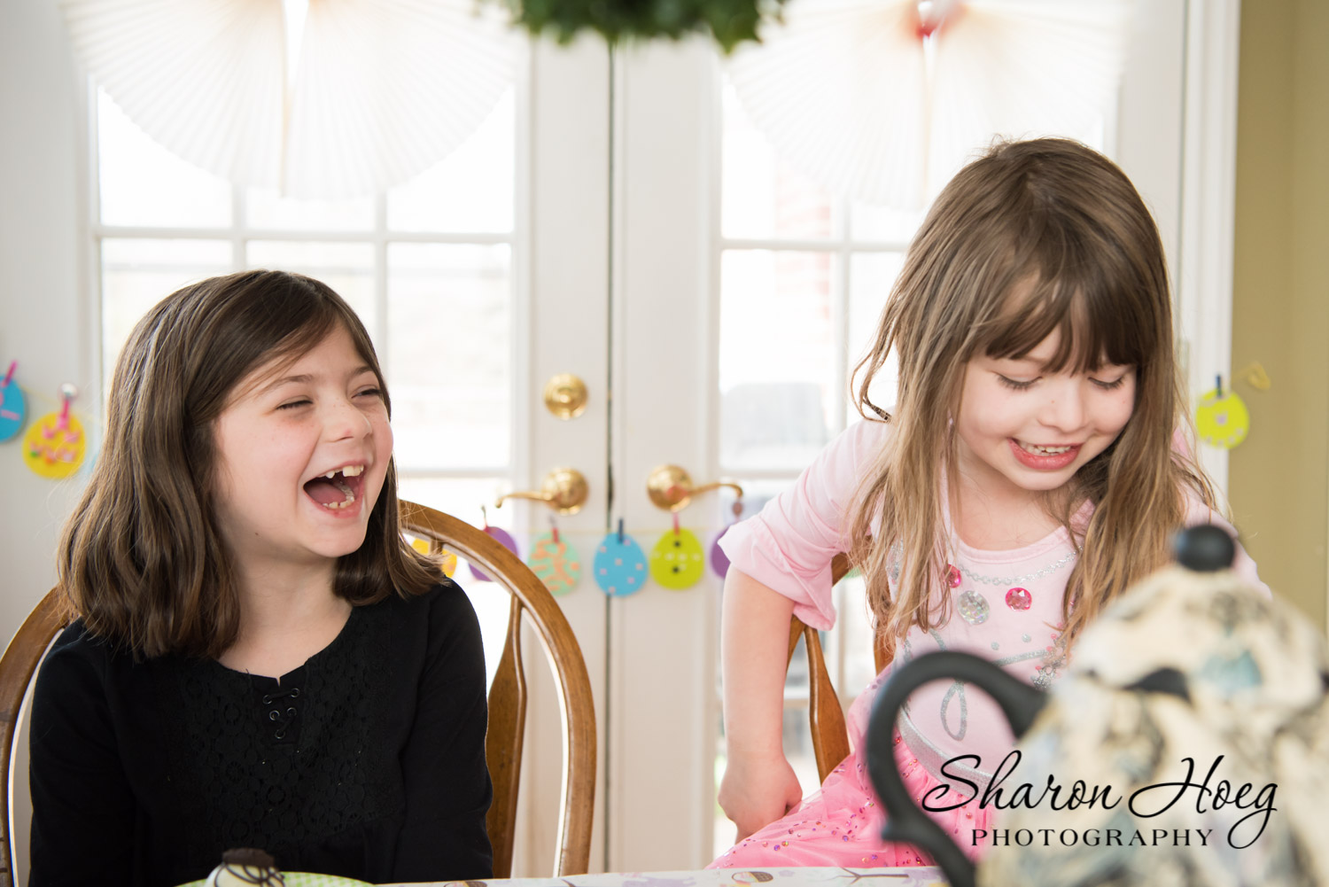 two happy sisters sitting at a spring table, Northville photographer