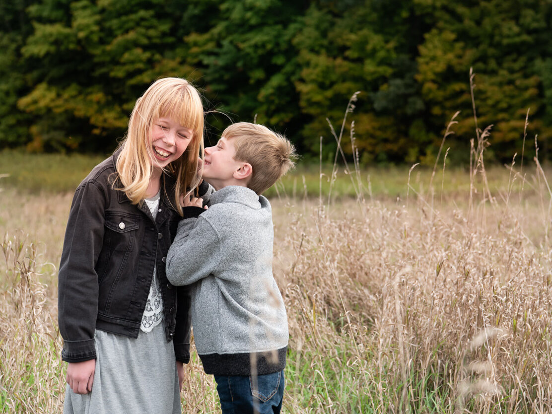 Boy whispering to sister. Livonia photographer near me