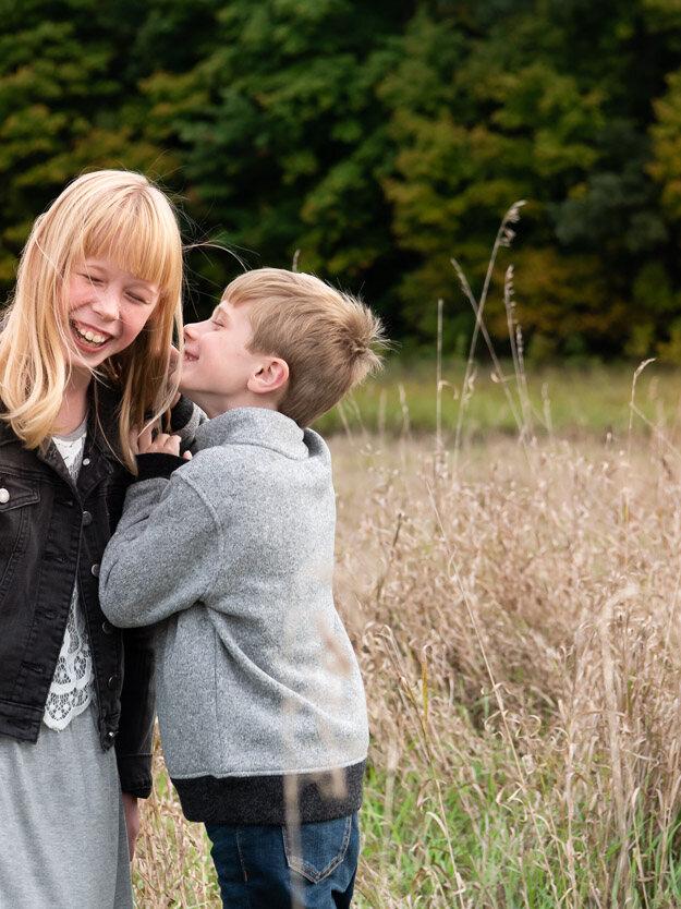 Boy whispering to sister. Livonia photographer near me